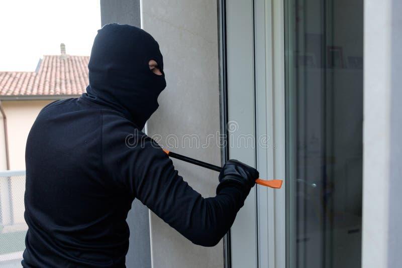 Cambrioleur essayant de forcer une serrure de porte utilisant le pied-de-biche images libres de droits