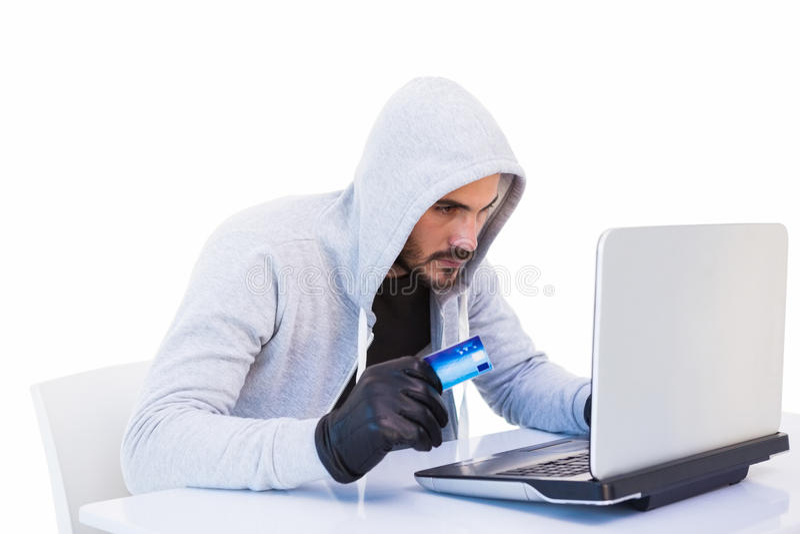 Cambrioleur faisant des achats en ligne avec l'ordinateur portable et la carte de crédit photos stock
