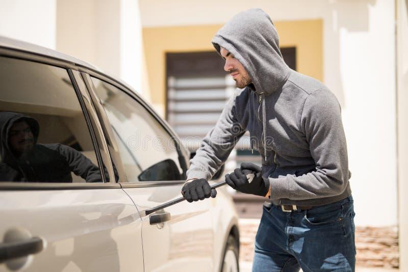 Cambrioleur forçant une portière de voiture images libres de droits