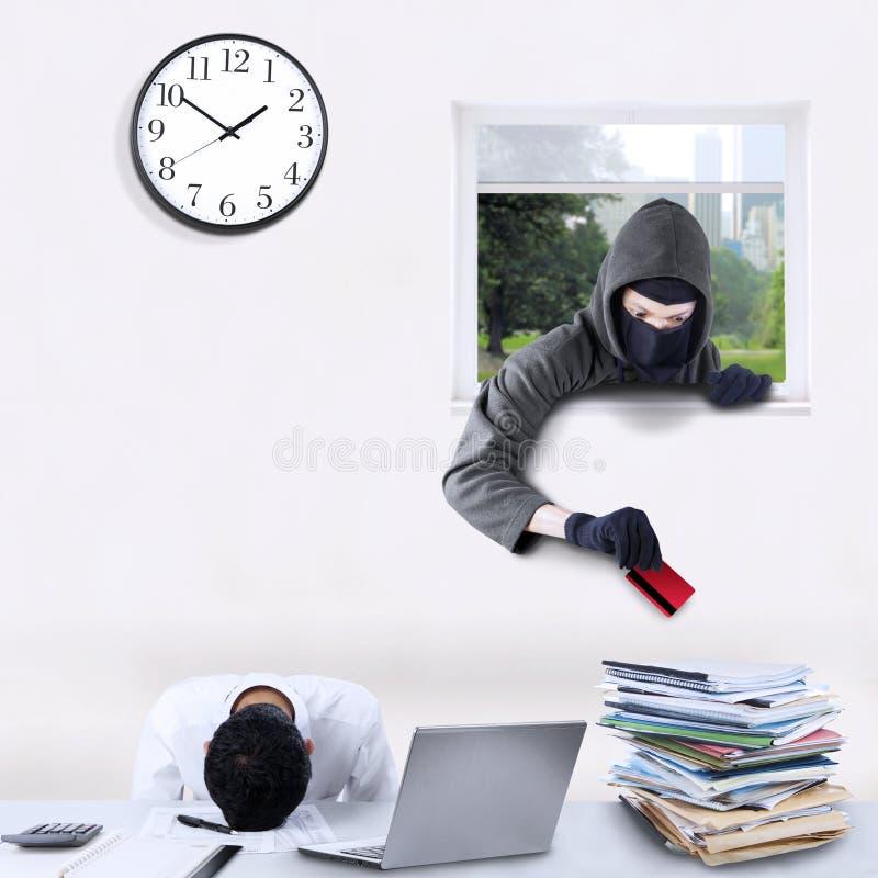 Cambrioleur volant la carte de crédit dans le bureau photos stock