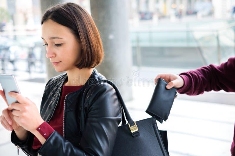 Cambrioleur volant le portefeuille d'argent du sac à main de distrait photo stock