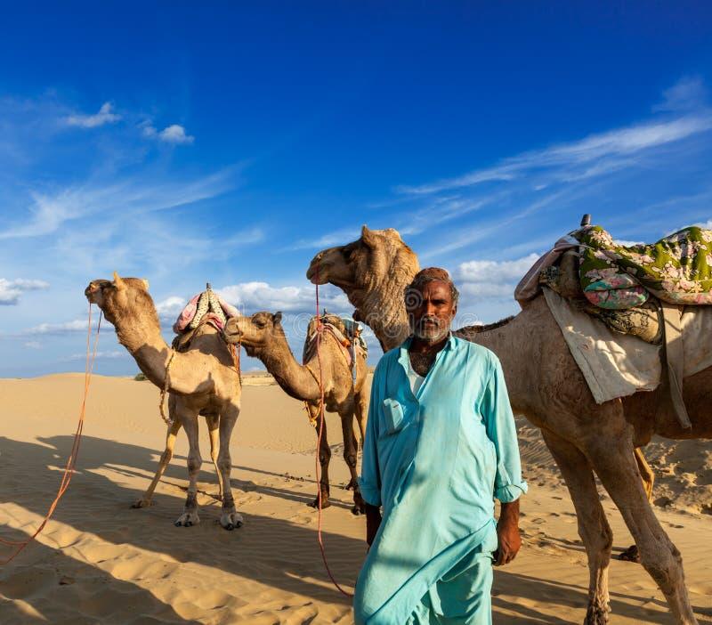 Cameleer (driver del cammello) con i cammelli in dune del deserto del Thar. Raj fotografia stock libera da diritti