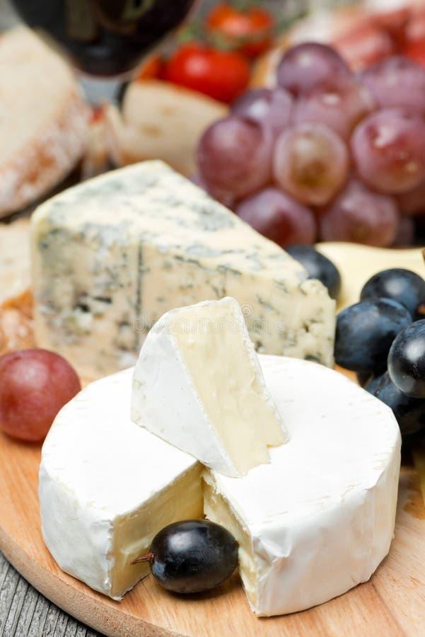 Camembert, błękitny ser, winogrona i orzechy włoscy na drewnianej desce, zdjęcia royalty free