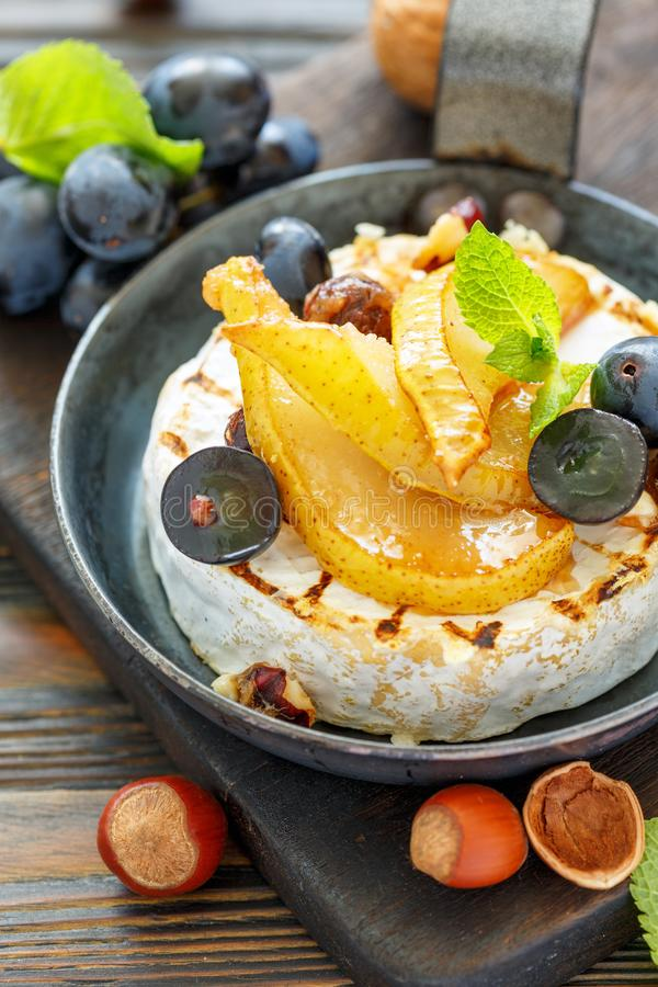 Camembert baked with pear and black grapes. royalty free stock photo