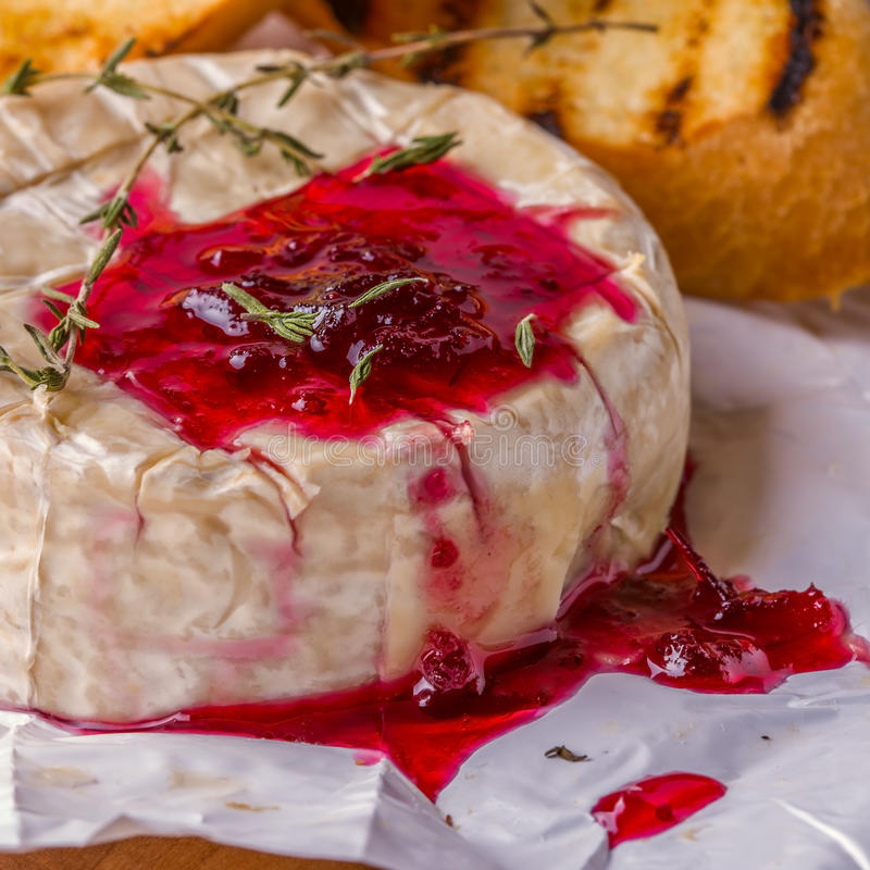 Camembert with berry jam, toast and thyme. stock photography