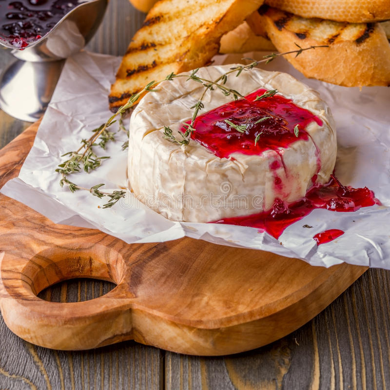 Camembert with berry jam, toast and thyme. stock photo