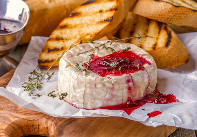 Camembert with berry jam, toast and thyme. royalty free stock images