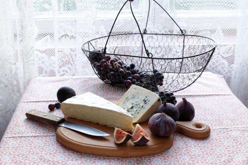 Cheeses, figs, and grape stock photography