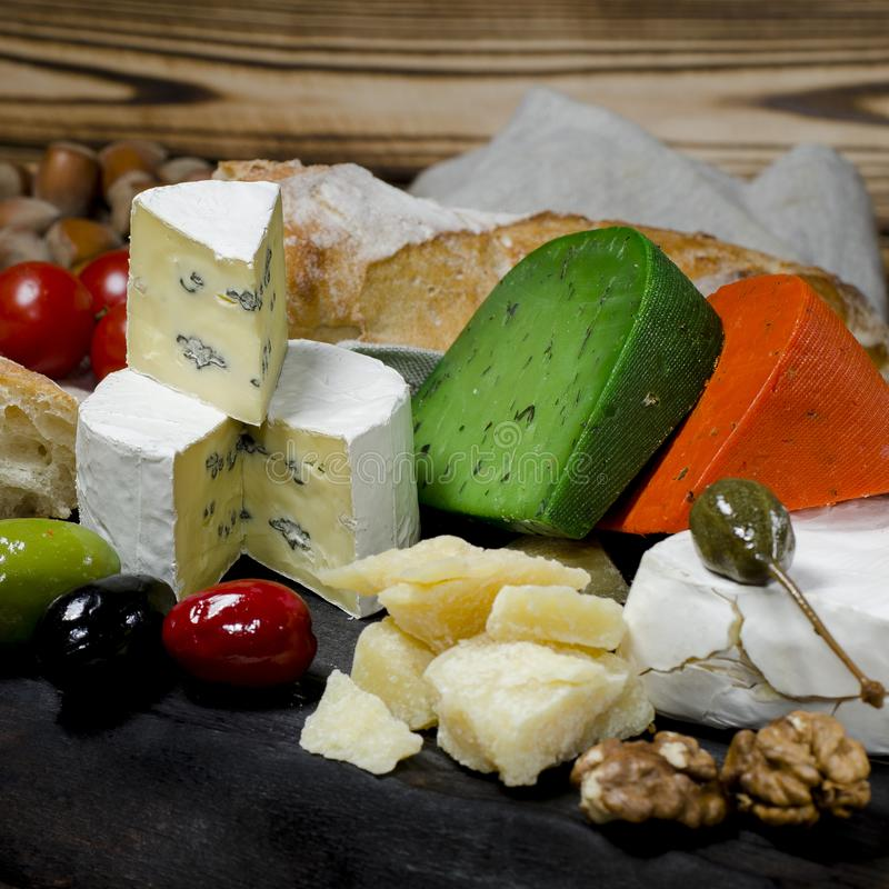 Mix cheese on dark background on wood board with grapes, honey, nuts, tomatoes and basil. Top view. Camembert, brie, parmesan cheese, green cheese with basil stock photography