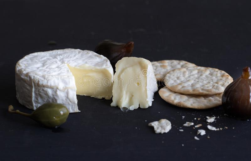 Camembert cheese, figs, caper berry and crackers on black background stock photography