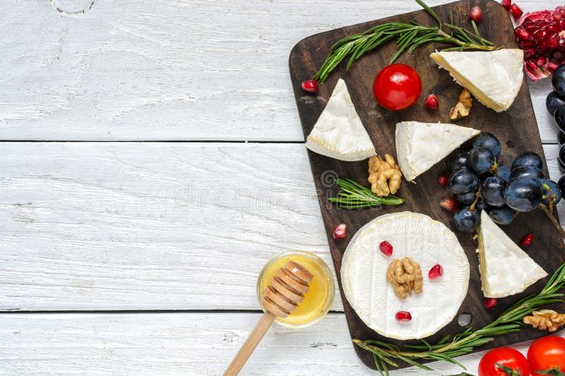 Camembert cheese with grapes, tomatoes cherry, pomegranate seeds, walnuts and rosemary on wooden cutting board stock images