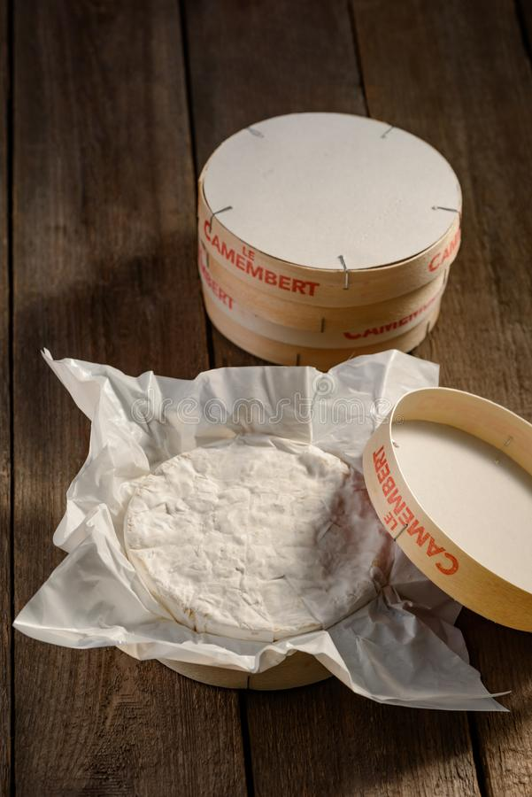 Camembert cheese in package. On wooden rustic table. White bloomy rind and soft creamy texture inside. French food royalty free stock photo