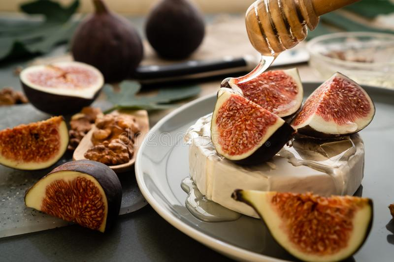 Camembert cheese with slices of ripe figs and honey. Still life of organic products and leaves of sweet fruits. stock images