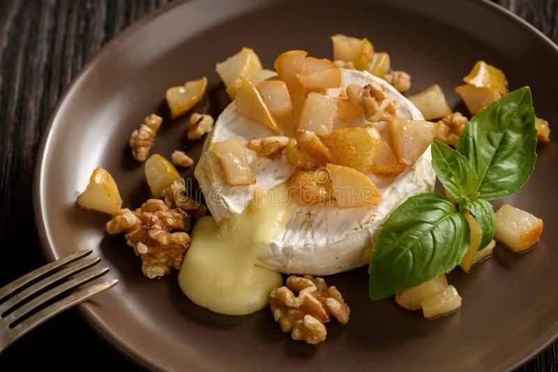 Camembert cocido con las peras y las nueces, servidas con el vino blanco fotografía de archivo