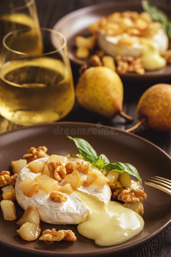 Camembert cocido con las peras y las nueces, servidas con el vino blanco fotografía de archivo libre de regalías