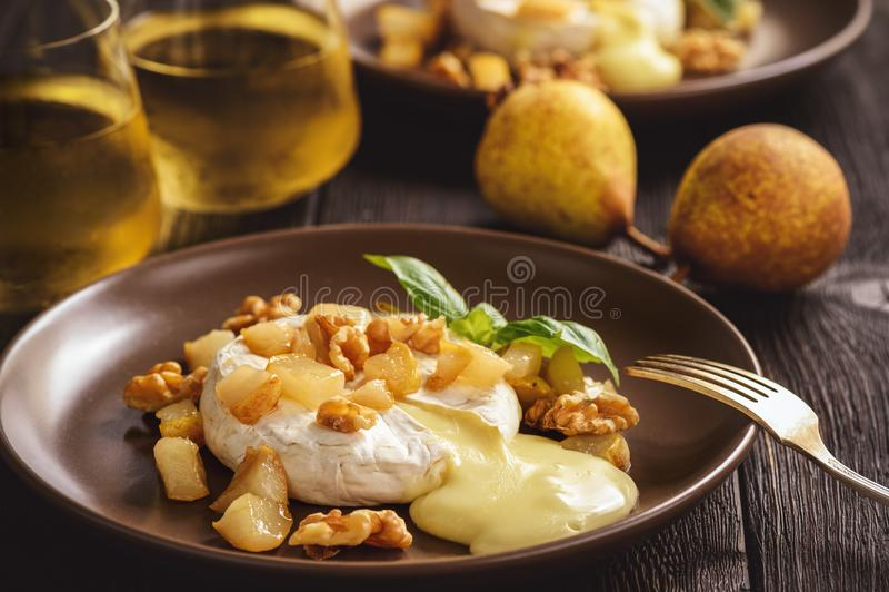 Camembert cocido con las peras y las nueces, servidas con el vino blanco imagen de archivo