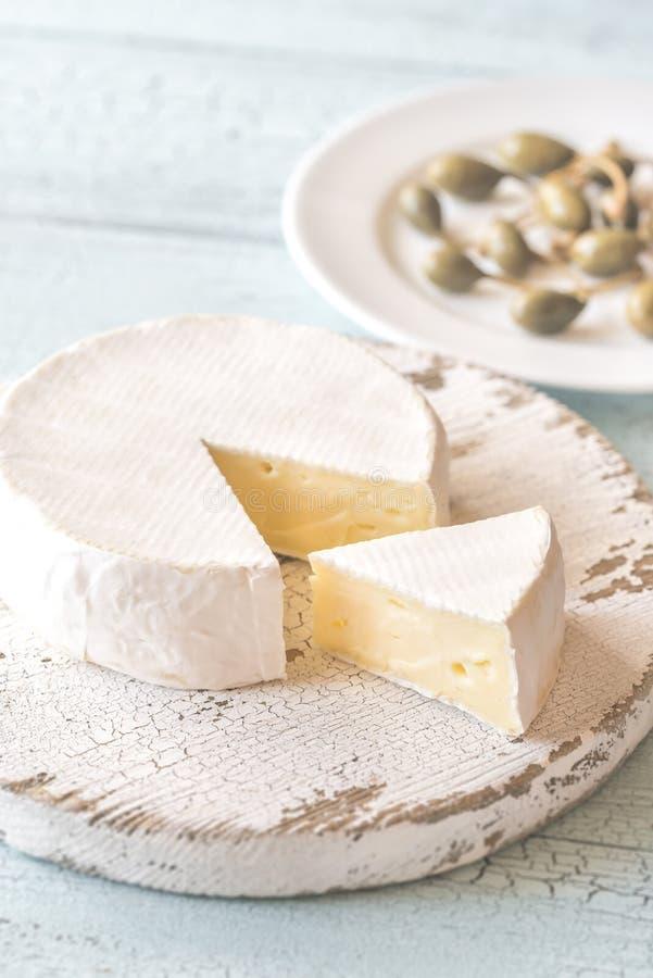Camembert com as alcaparras na placa de madeira imagens de stock