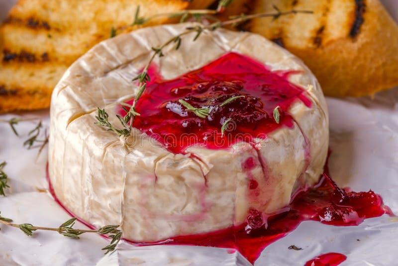 Camembert con el atasco, la tostada y el tomillo de la baya foto de archivo