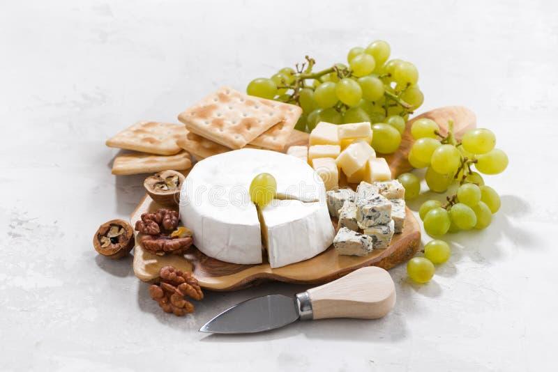 Camembert, druvor och smällare på en vit bakgrund royaltyfri foto