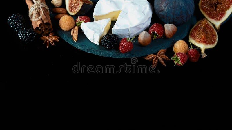 Camembert- eller brieost med fikonträd och bär av björnbär och hallon på en skiffer stiger ombord på en svart bakgrund, Fl royaltyfria bilder