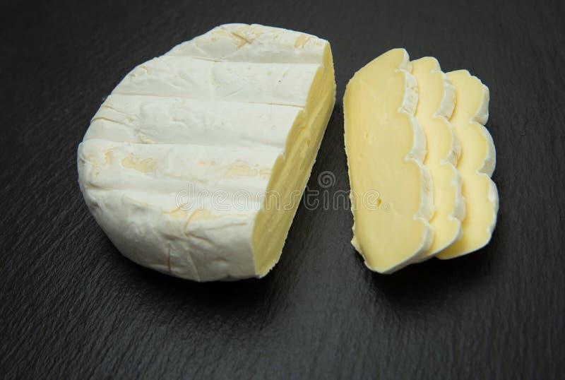 camembert Fromage crémeux mou coupé en tranches sur le fond foncé image libre de droits