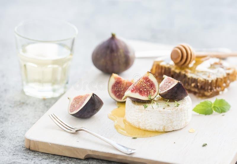 Camembert oder Brie mit frischen Feigen, Bienenwabe und Glas Weißwein auf Umhüllung verschalen über rustikalem Grau des Schmutzes stockfotografie