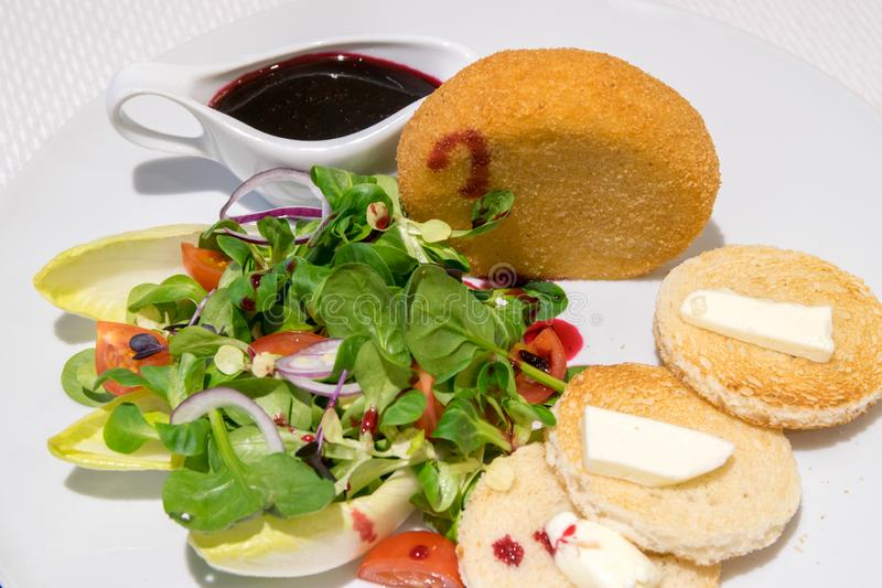 Camembert pane with cranberries sauce, butter, salad, and French toast royalty free stock photos