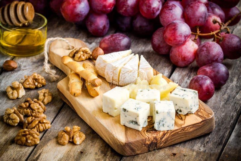 Camembert, parmesano, queso verde con las barras de pan, nueces, miel y uvas foto de archivo libre de regalías