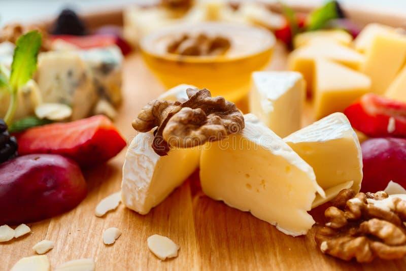 Camembert plasterki z winogronami, orzechami włoskimi i miodem, obraz stock