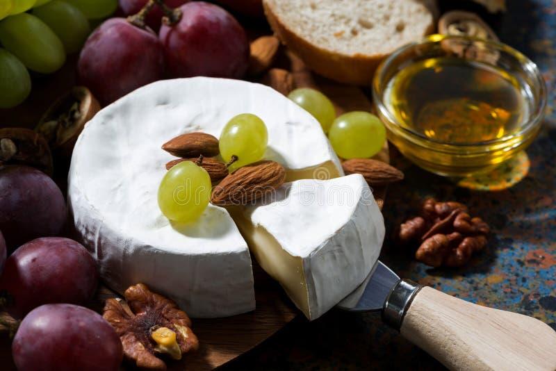 Camembert ser, owoc i miód na ciemnym tle, obrazy stock