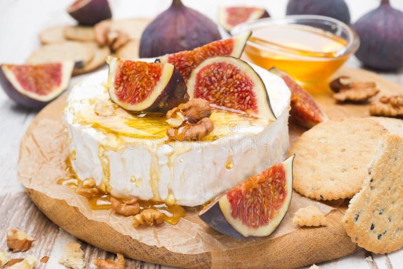 Camembert ser z miodem, figami i krakers na drewnianej desce, zdjęcia royalty free