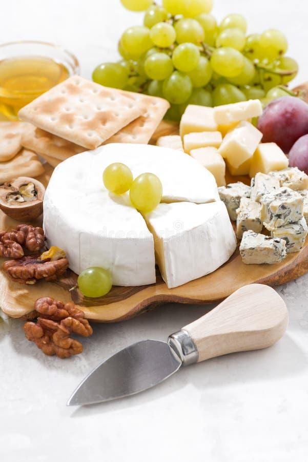 Camembert, winogrona i krakers na białym stole, pionowo obrazy royalty free