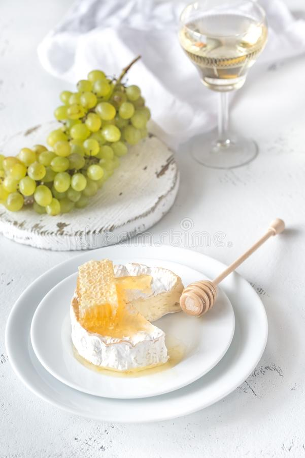Camembert z miodem, winogronami i białym winem, obrazy stock