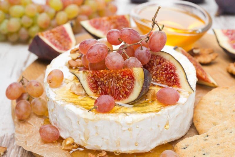 Camembert z winogronami, figami, miodem i orzechami włoskimi na drewnianej desce, obraz stock