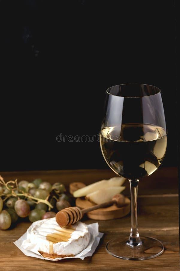 CamembertBrie med Honey Grape och exponeringsglas av vitt vin på ost och frukt för träbakgrund mjuk på träbrädeost och royaltyfri bild