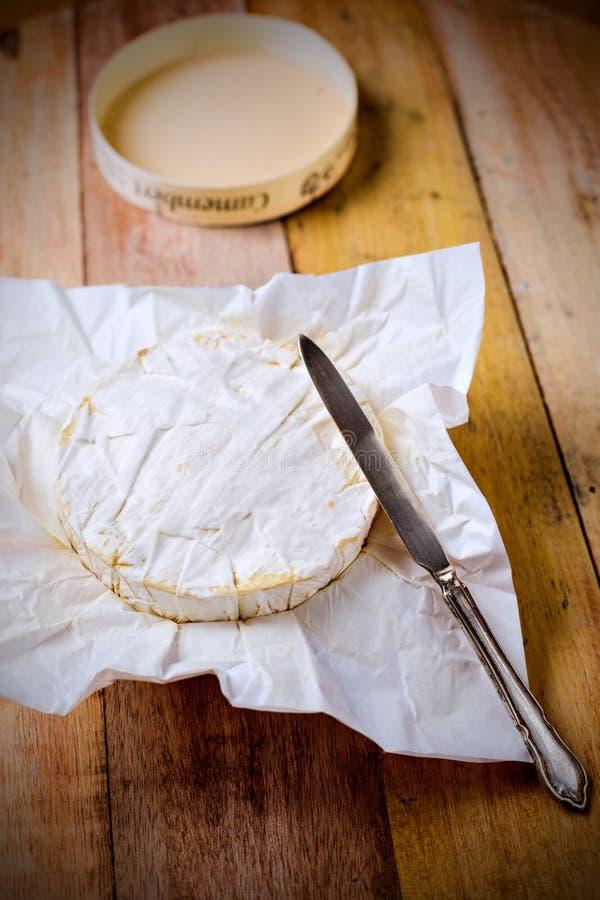 Camembertkaas in document met uitstekend mes op houten t wordt verpakt dat royalty-vrije stock foto