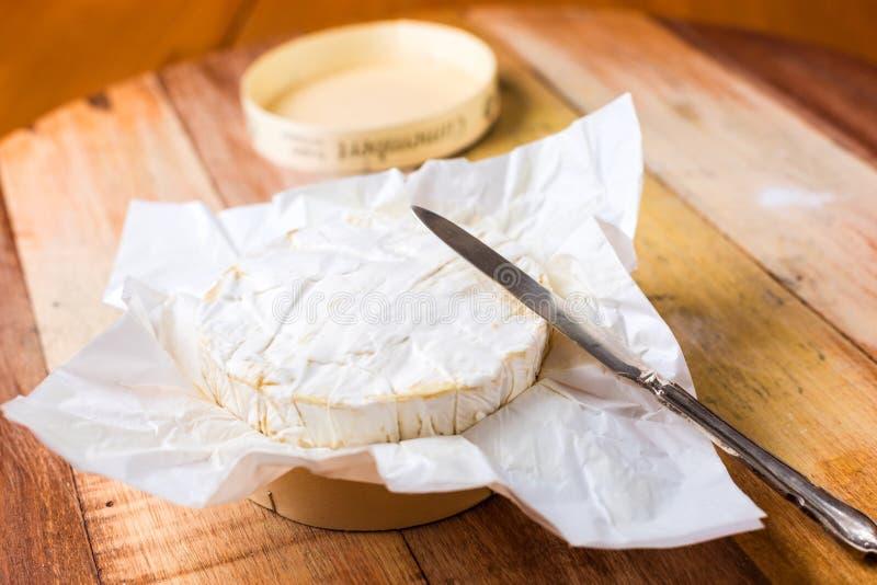 Camembertkaas in document met uitstekend mes op houten t wordt verpakt dat stock afbeelding