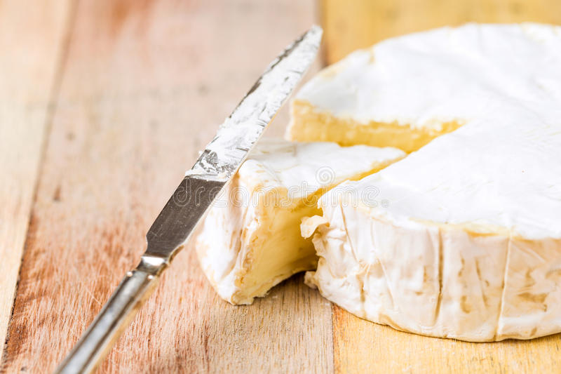 Camembertkaas en uitstekend mes stock fotografie