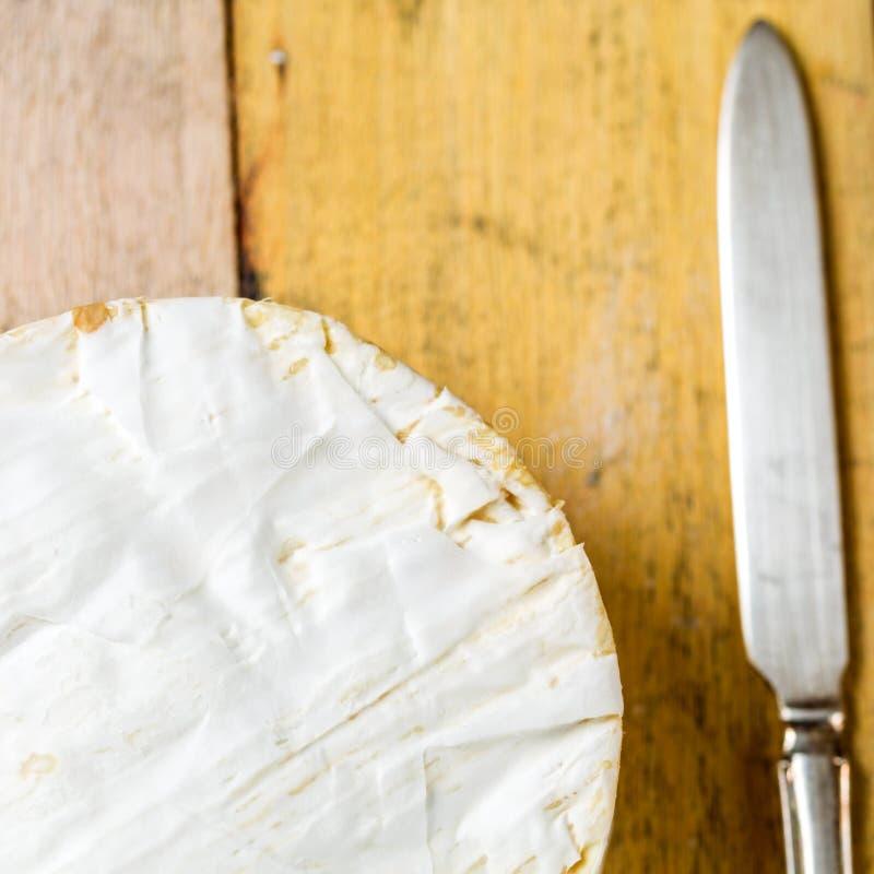 Camembertkaas en uitstekend mes op houten lijst royalty-vrije stock afbeeldingen