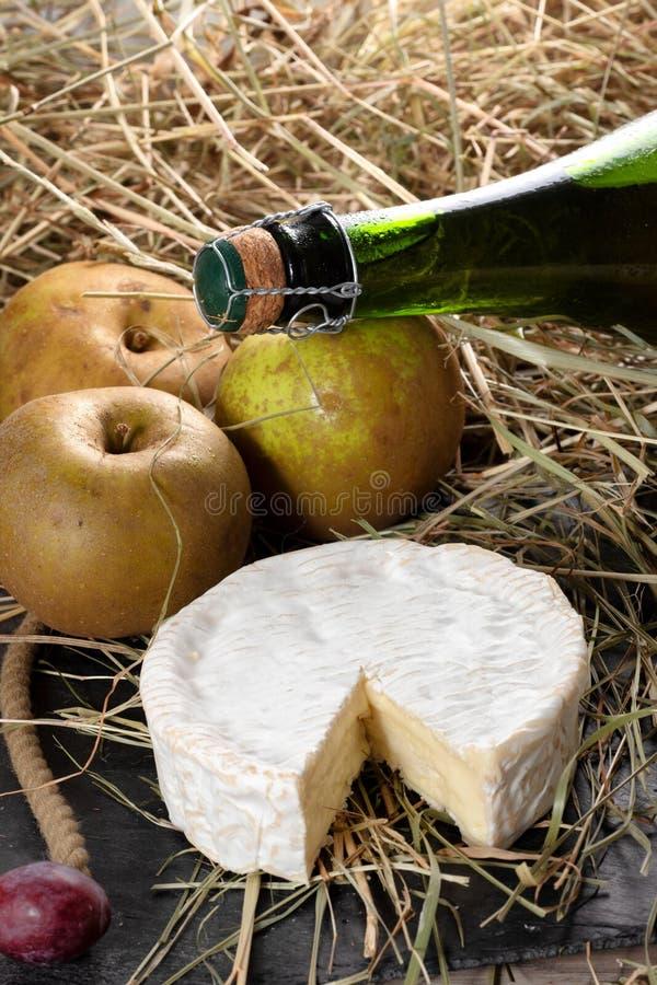 Camembertkaas, fles cider en appelen royalty-vrije stock afbeeldingen
