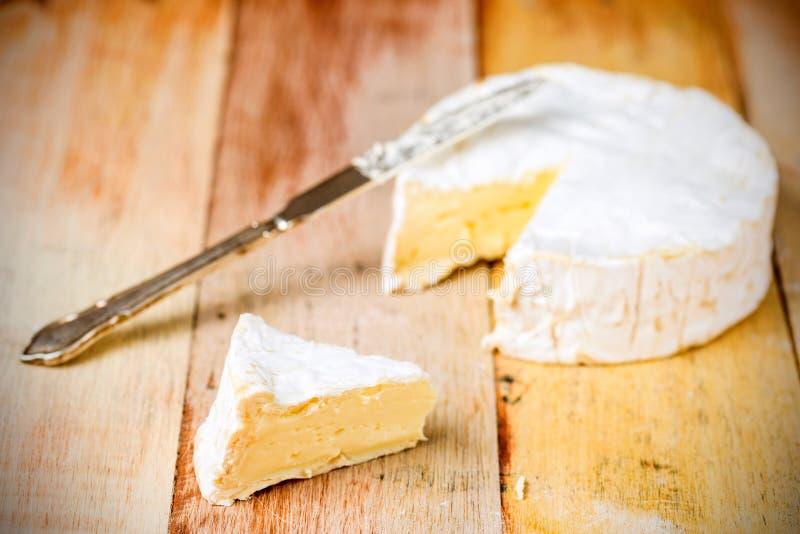 Camembertkaas met besnoeiingswig en uitstekend mes stock fotografie