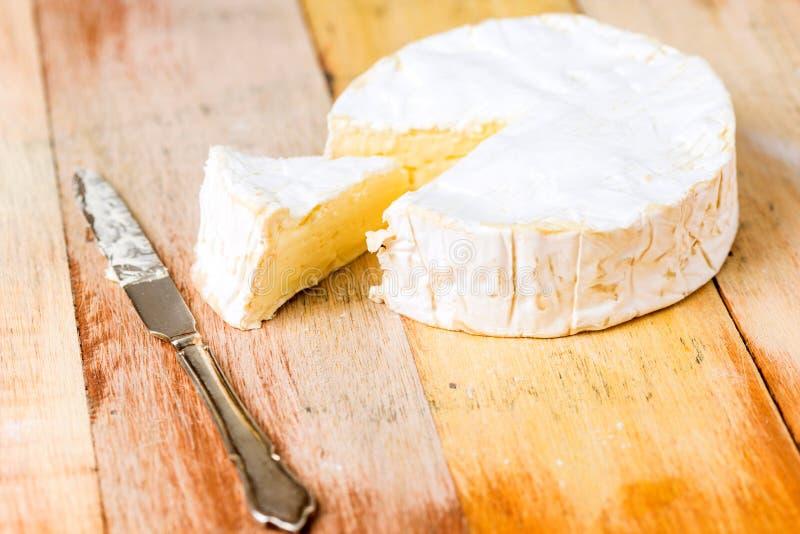 Camembertkaas met besnoeiingswig en uitstekend mes op houten tabl royalty-vrije stock afbeeldingen