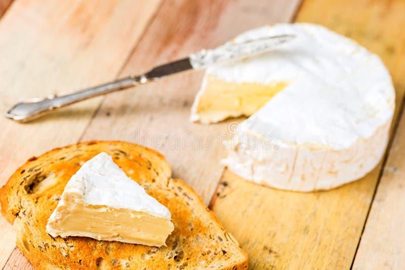 Camembertkaas met besnoeiingswig op geroosterde broodplak en vinta stock afbeeldingen
