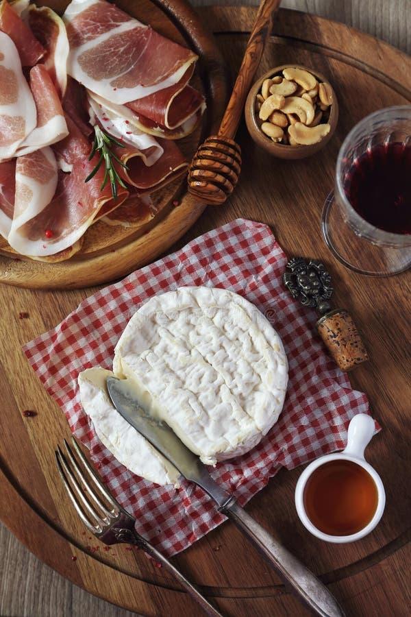 Camembertost, kallskuret och rött vin royaltyfri fotografi