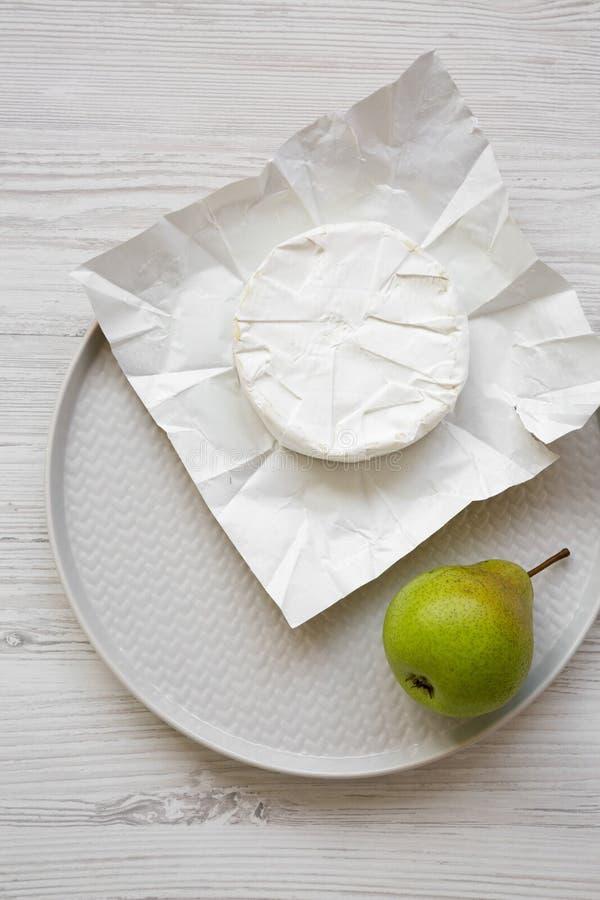 Camembertost på papper, nytt päron på en platta Mat f?r vin Över huvudet, framlänges lekmanna- bästa sikt, från över fotografering för bildbyråer