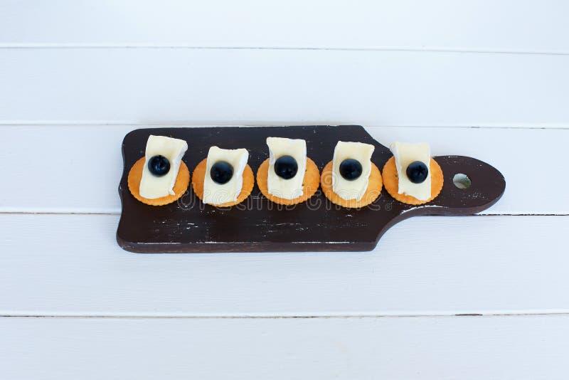 Camembertostoliv och smällare Medelhavs- banta och kokkonst på vit bakgrund royaltyfria foton