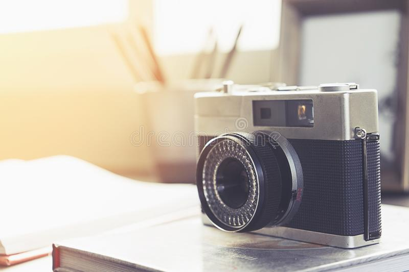 Camera,book and pens on a wooden table. In front of the window royalty free stock photo