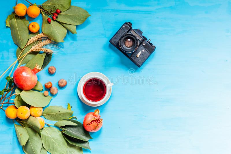Autumn fruits, nuts, pomegranate on blue background. Camera coffee cup fruit nuts on a blue background stock photography