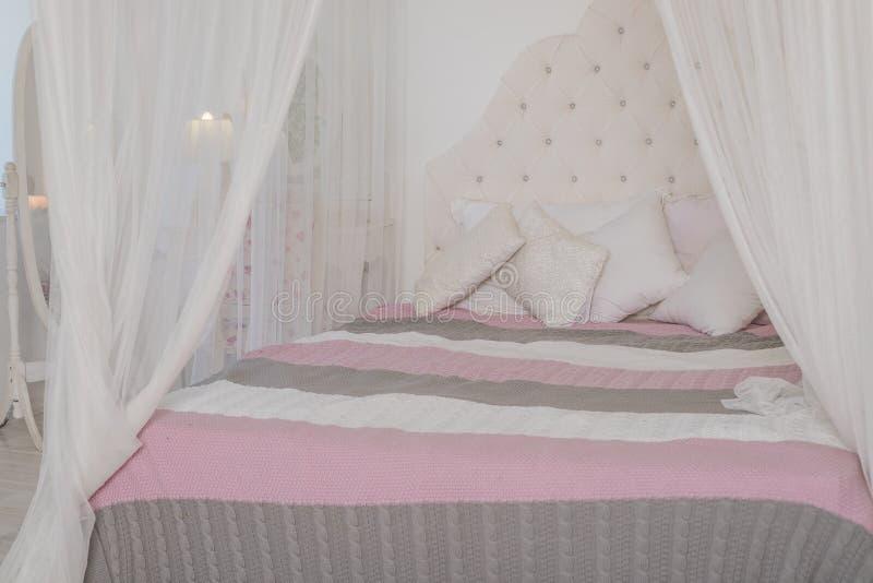 Camera da letto accogliente nei colori pastelli leggeri, un grande letto a baldacchino con i cuscini Progettazione scandinava di  fotografia stock