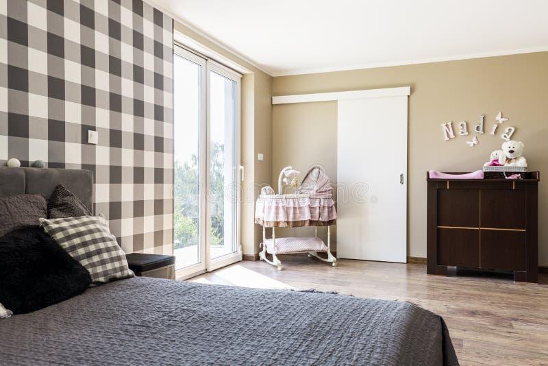 Camera da letto beige con un angolo neonato del ` s fotografia stock libera da diritti